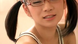 Skinny Japanese chick Ami Tokito wears her glasses. She is in her bedroom, but I guess she is not even going to striptease!