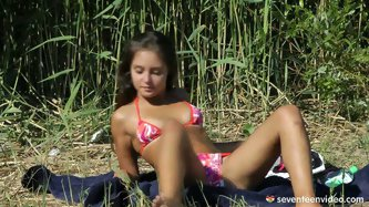 Sexy brunette teen with tasty tanned body takes sunbath by the pond where she decides to please her shaved cunt with fingers.