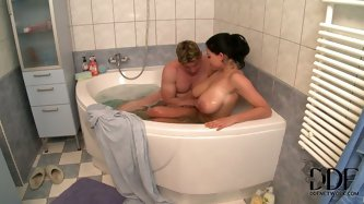 A huge guy with big dick is in the hot tub with a busty brunette babe. He is sucking on those sweet big tits and soft nipples.
