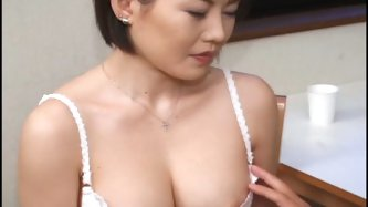 Sensual black haired pale skin mom from Japan named Kiyomi sits on the chair in her white neglige while dude licks and tickles her pink nipples.