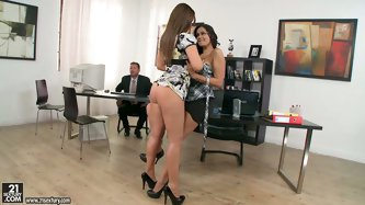 Two outstanding babes in the office are horny. They seduce their male colleague for a threesome by making out in the middle of the office. That horny