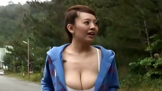 Watch Hitomi Tanaka jiggling boobies while she runs on the high way and later pours cold water on her giant natural breasts.