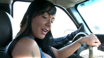 Lascivious raven haired mommy drives car on a highway and jacks off her partner's massive dick at the same time. Horny MILF looks fucking hot as