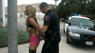 Trashy looking prostitute Bree Olson smokes sitting on the road. Cop puts cuffs on her hands and starts to play with her pussy in the car.