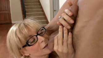 Slutty blonde wife Nina Hartley gives blowjob to young man and teases her pussy with fingers. When the cock is hard and ready she rides him on the cou