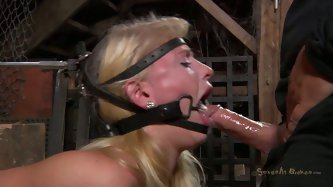 "Spoiled blond chic gets her body tied to massive table and her face ""decorated"" with muzzle while she rides a dildo and receives a wil"