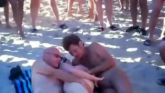 Hubby is sharing his wife with a strangers at the beach of Cap d'Agde. Lots of people is watching. More beach sex videos on x<vidz69.