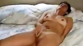 Lying on her back in bed with legs apart, this tanlined mature amateur vigorously rubs her clitoris. As the arousal escalates, the movement of her fin